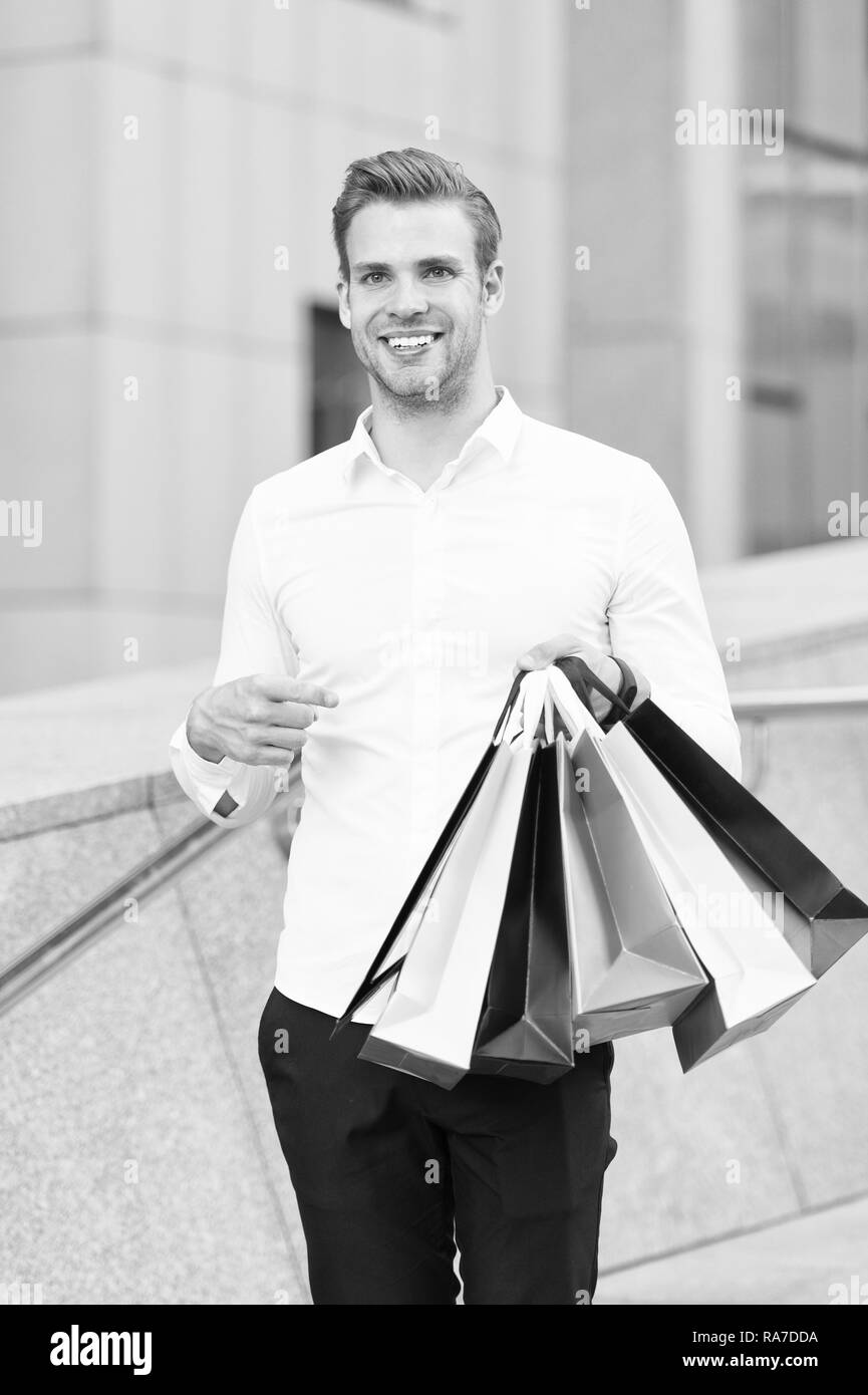 Man formal clothes carry shopping bags. Guy happy carry bunch shopping bags. Profitable deals on black friday. Man hold lot paper bags packages after shopping in mall. Black friday sale concept. Stock Photo
