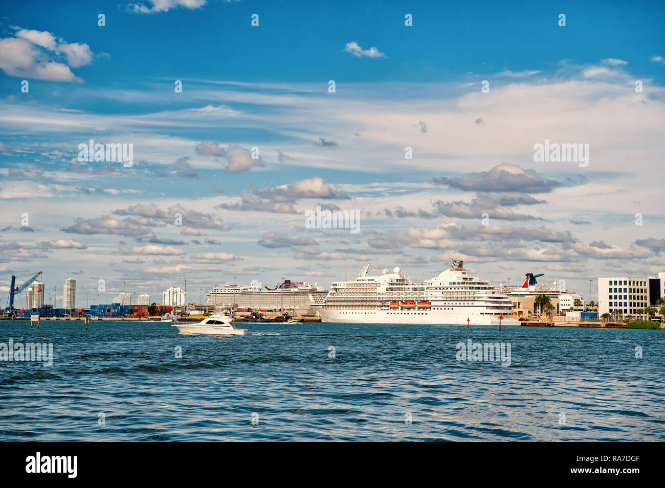 Miami, USA - February 29, 2016: luxury white sea or ocean liner cruise ship at city harbor or port on sea water surface or moorage on sunny day on blue sky - Stock Image