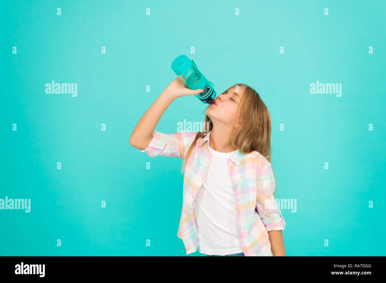 Kid hold bottle blue background. Water balance concept. Healthy and hydrated. Pediatric disorders of water balance. Girl cares about health and water balance. Child girl long hair has water bottle. - Stock Image