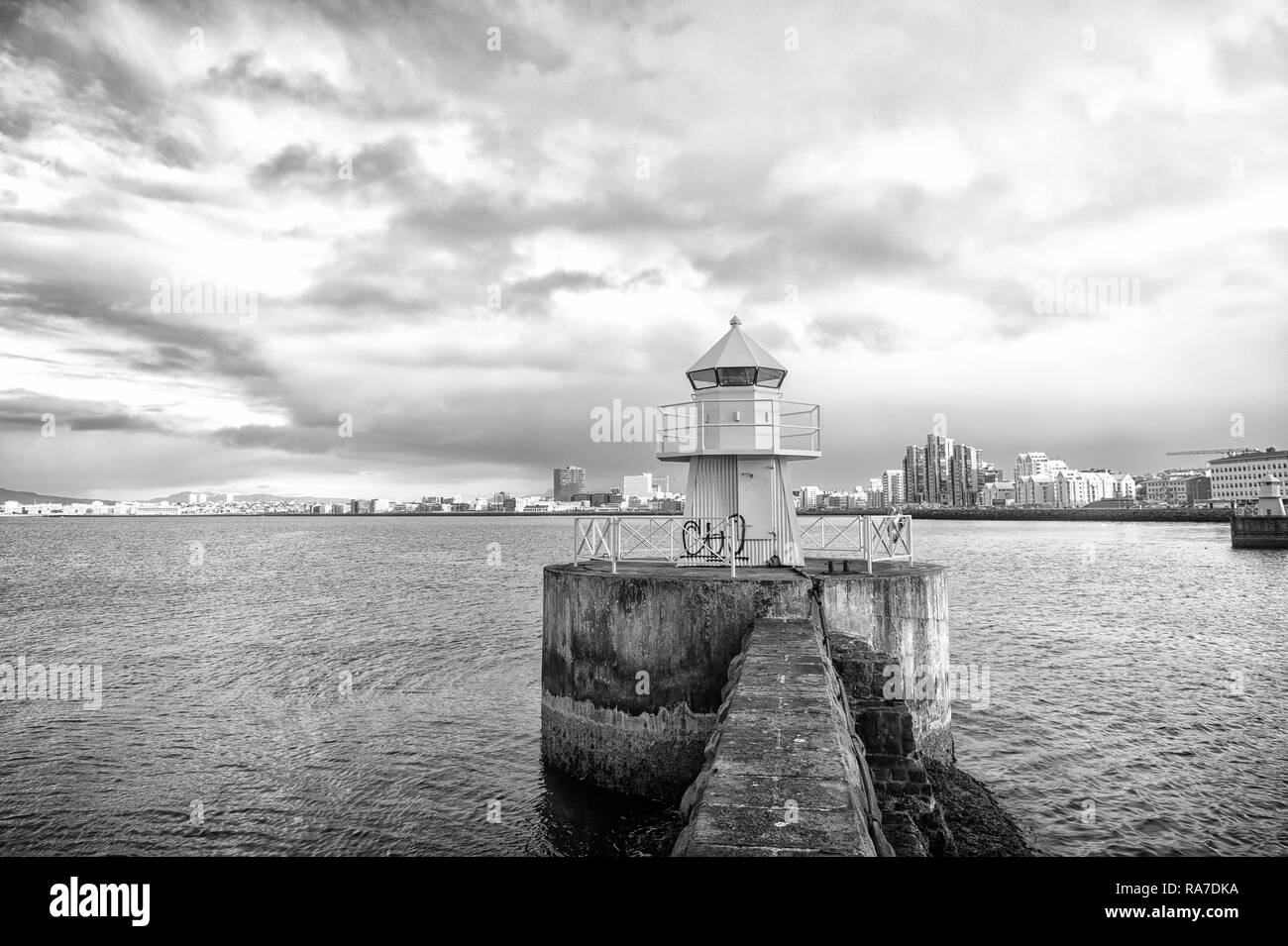 Lighthouse tower on stone pier in reykjavik, iceland. Lighthouse in sea. Seascape and skyline on cloudy sky. Architecture structure and design. Navigational aid concept. Wanderlust and travelling. - Stock Image