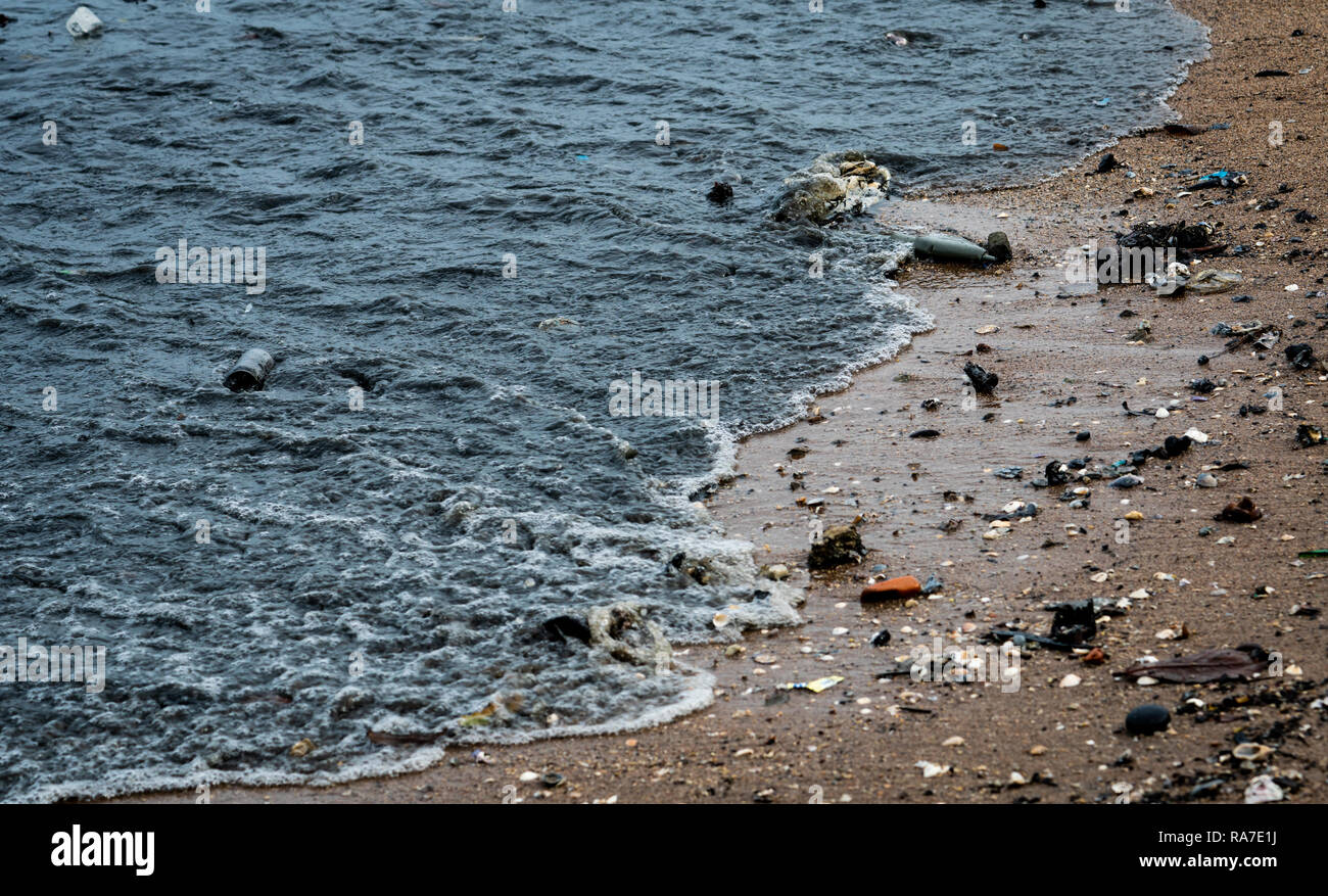 Beach environment pollution. Oil stains on the beach. Oil leak to the sea. Dirty water in the ocean. Water pollution. Harmful for animal in the ocean  - Stock Image