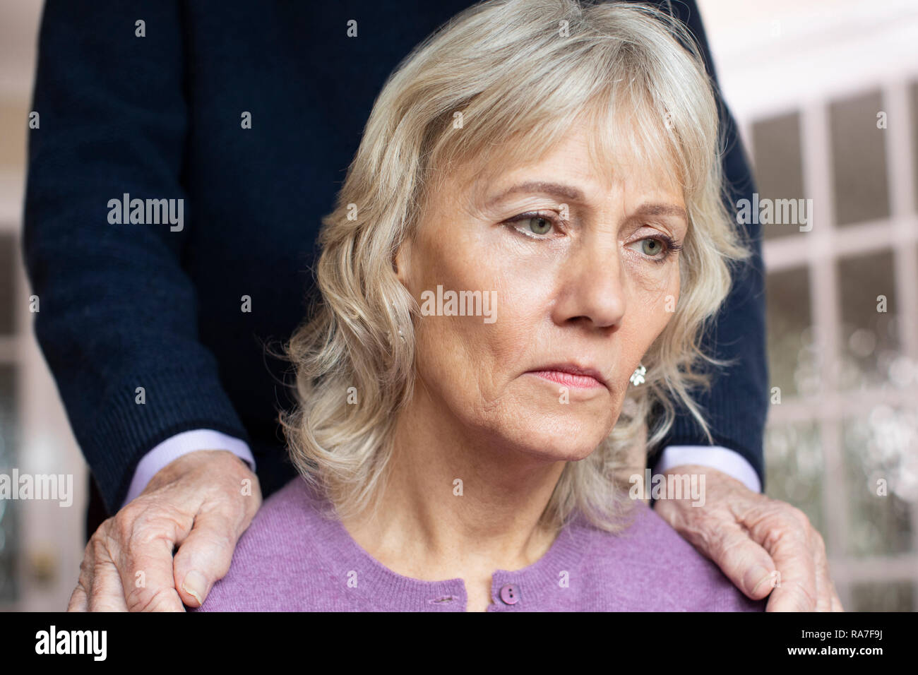 Confused Senior Woman Suffering With Depression And Dementia Being Comforted By Husband - Stock Image