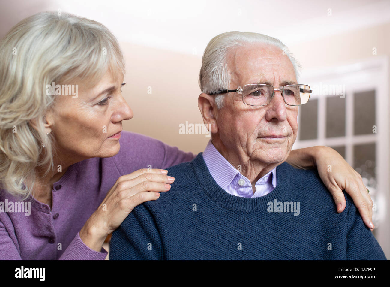 Confused Senior Man Suffering With Depression And Dementia Being Comforted By Wife Stock Photo