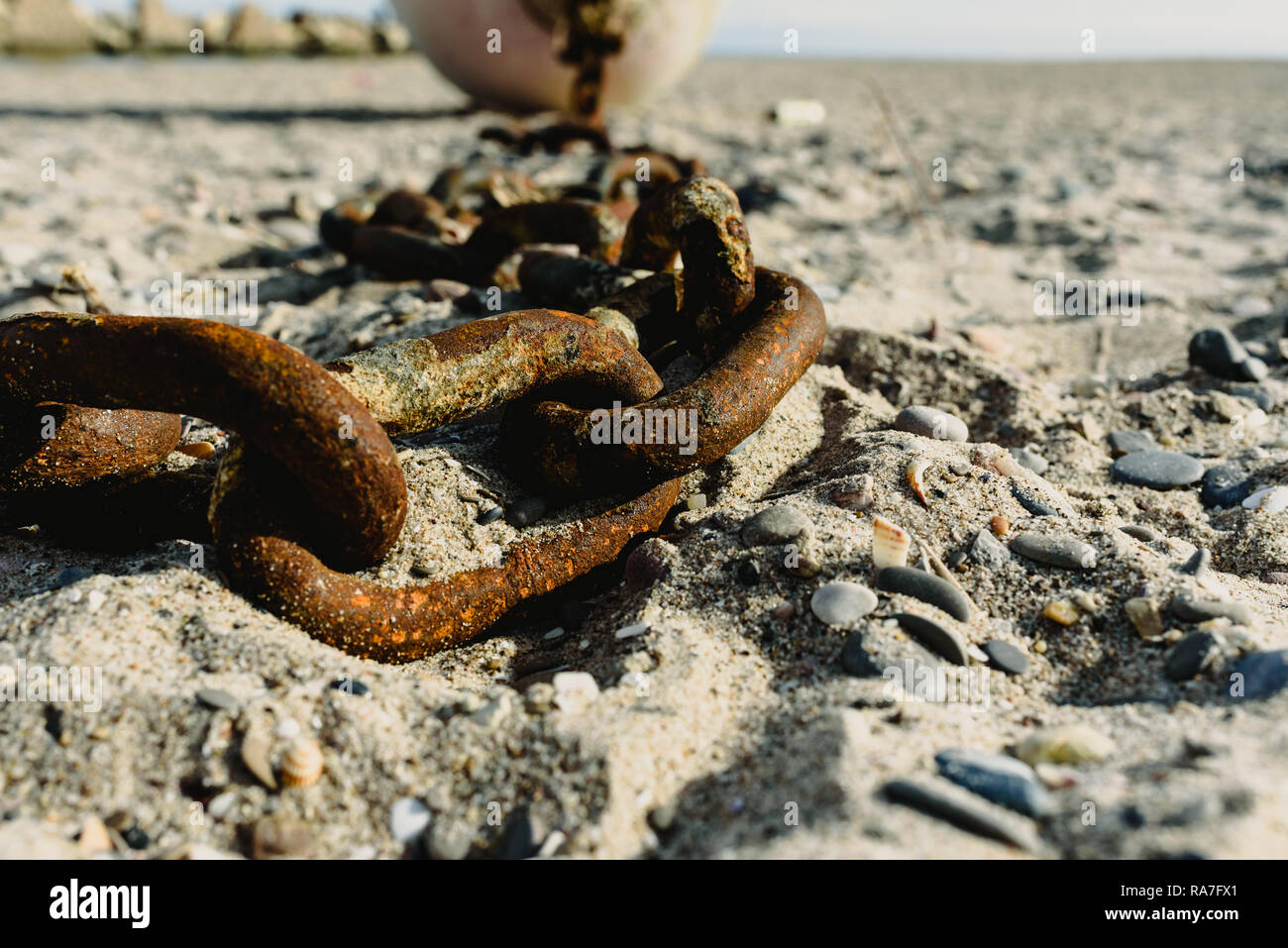 Concept of abandonment, old rusty and broken chains thrown in the sand of a dirty beach. - Stock Image