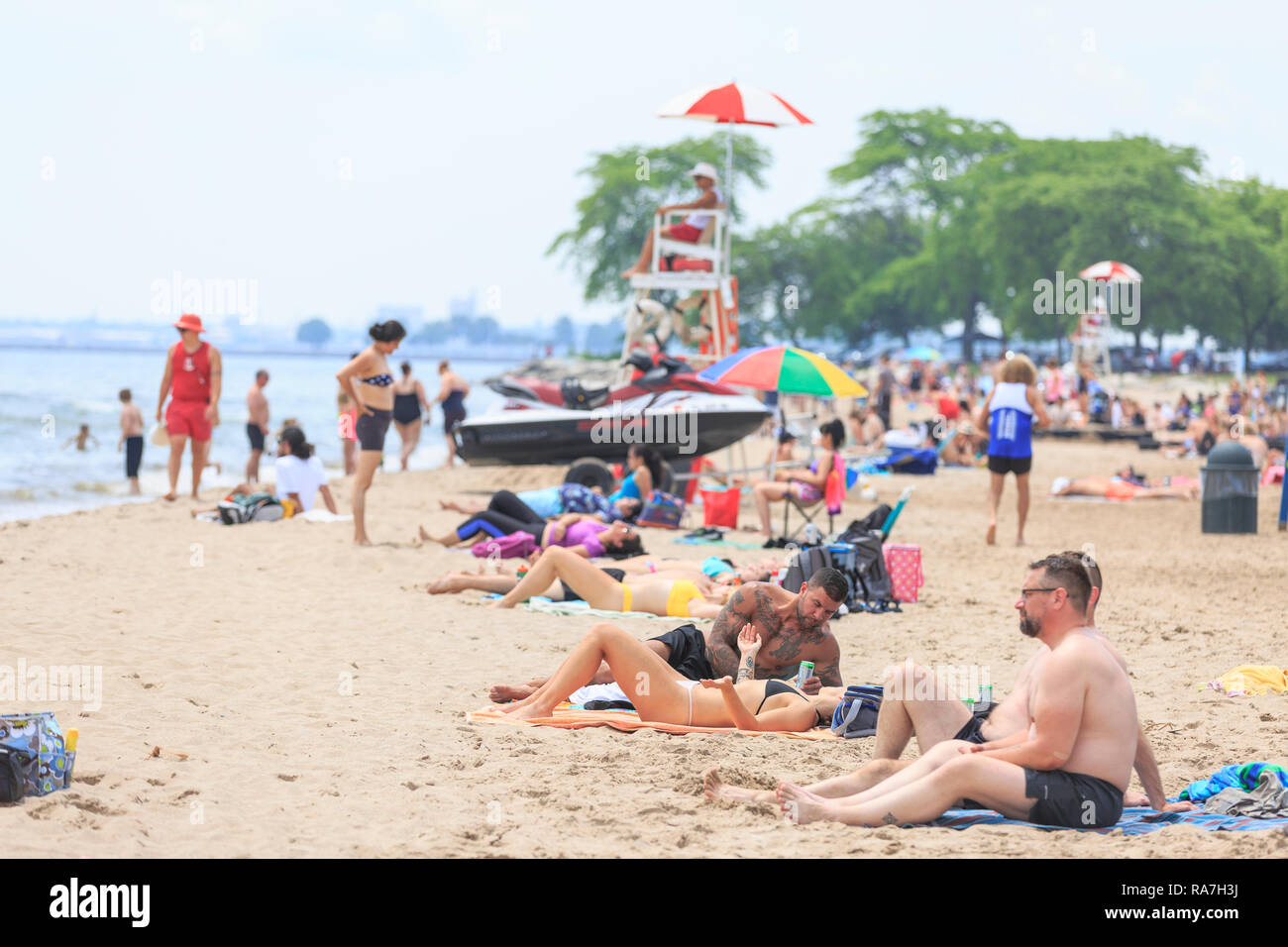 crowds of people fill a beach on a hot summer day - Stock Image
