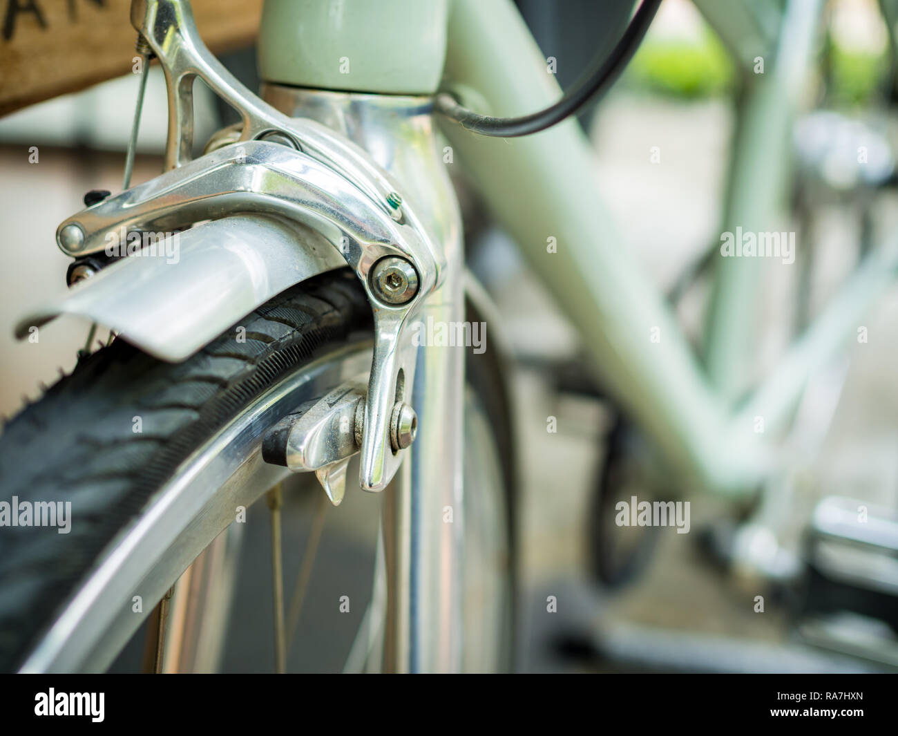 Close-up bicycle brakes and wheel on green vintage bicycle with copy