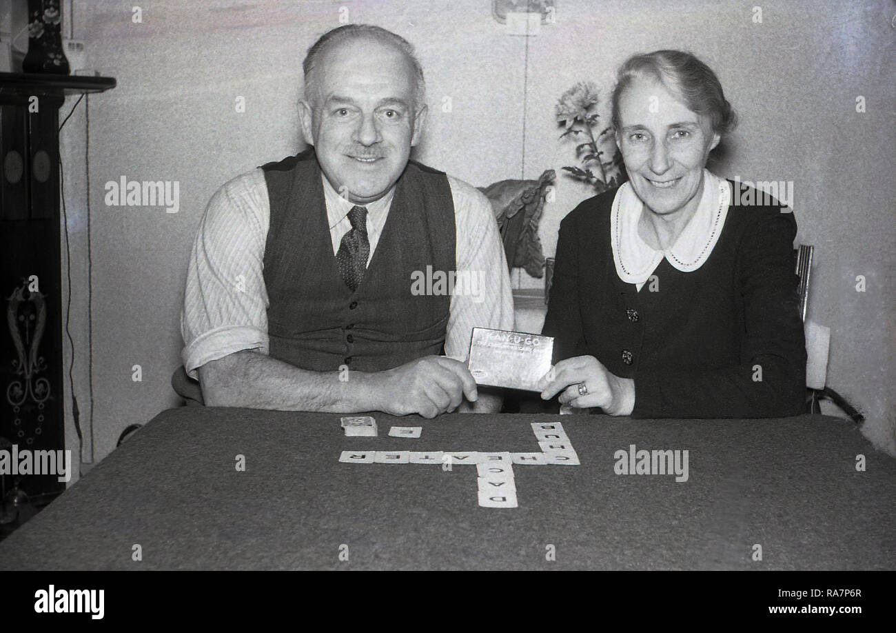 1950, elderly couple sitting at a card table playing 'Kan-U-Go', an old crossword card game, England, UK. For two to seven players, the game originates from the 1930s and has small cards with letters and values and simple rules for playing and scoring, - Stock Image