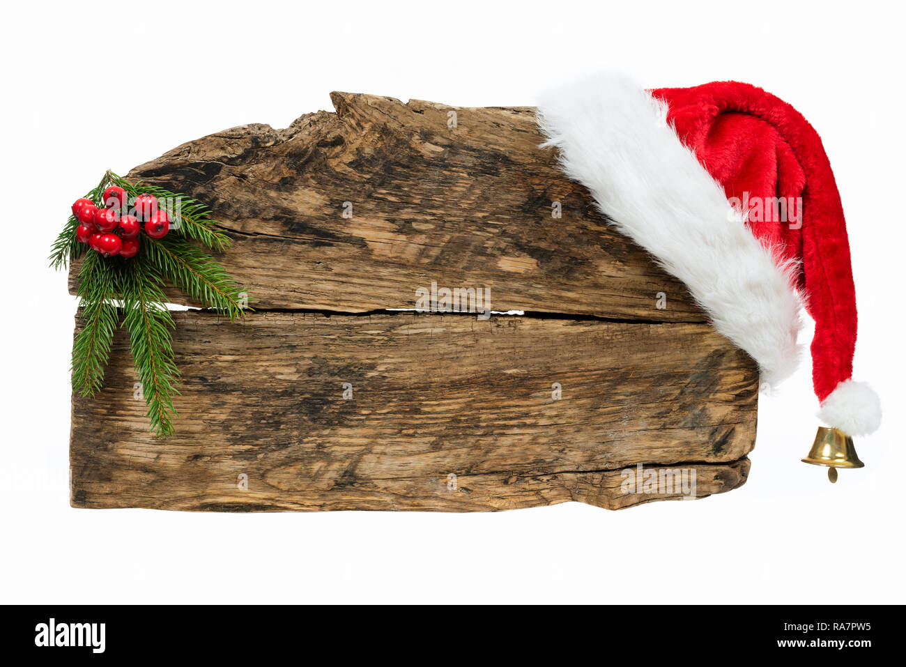 Christmas template - old wooden sign with Santa hat and spruce twig on white background - Stock Image