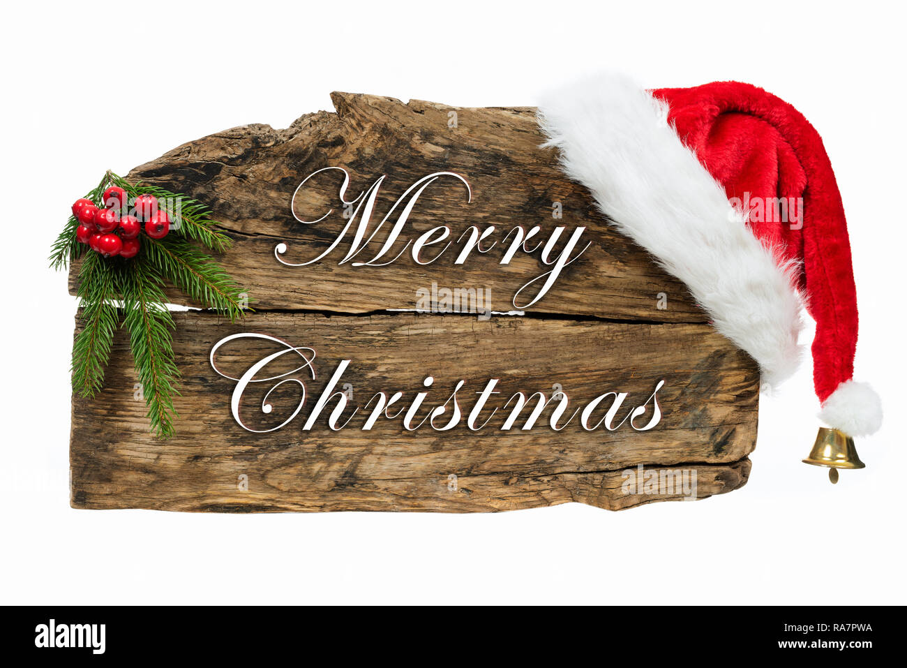 Christmas decoration - old wooden board sign with Santa hat and spruce twig on white background - Stock Image