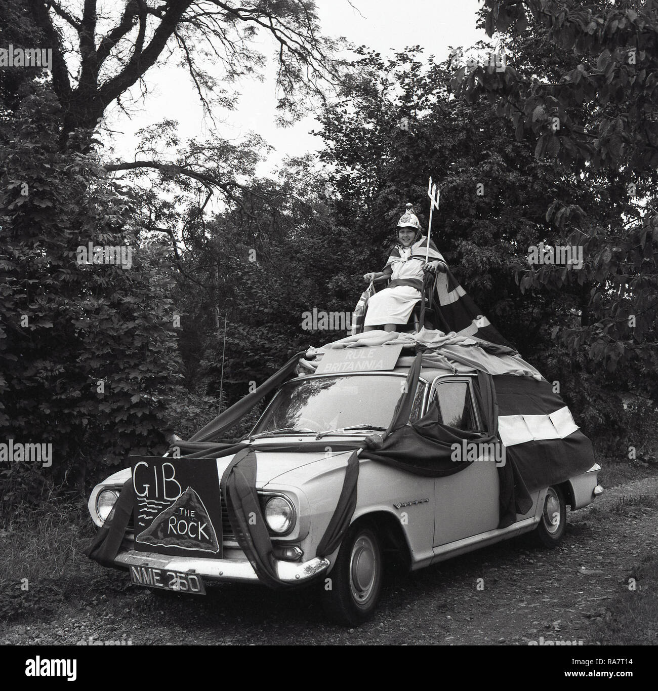 1967, Prestwood village fete, young girl in fancy dress and with a Union Jack cape sitting on a chair fixed on the top of a decorated car  with a 'Rule Britannia' sign on it, England, UK - Stock Image