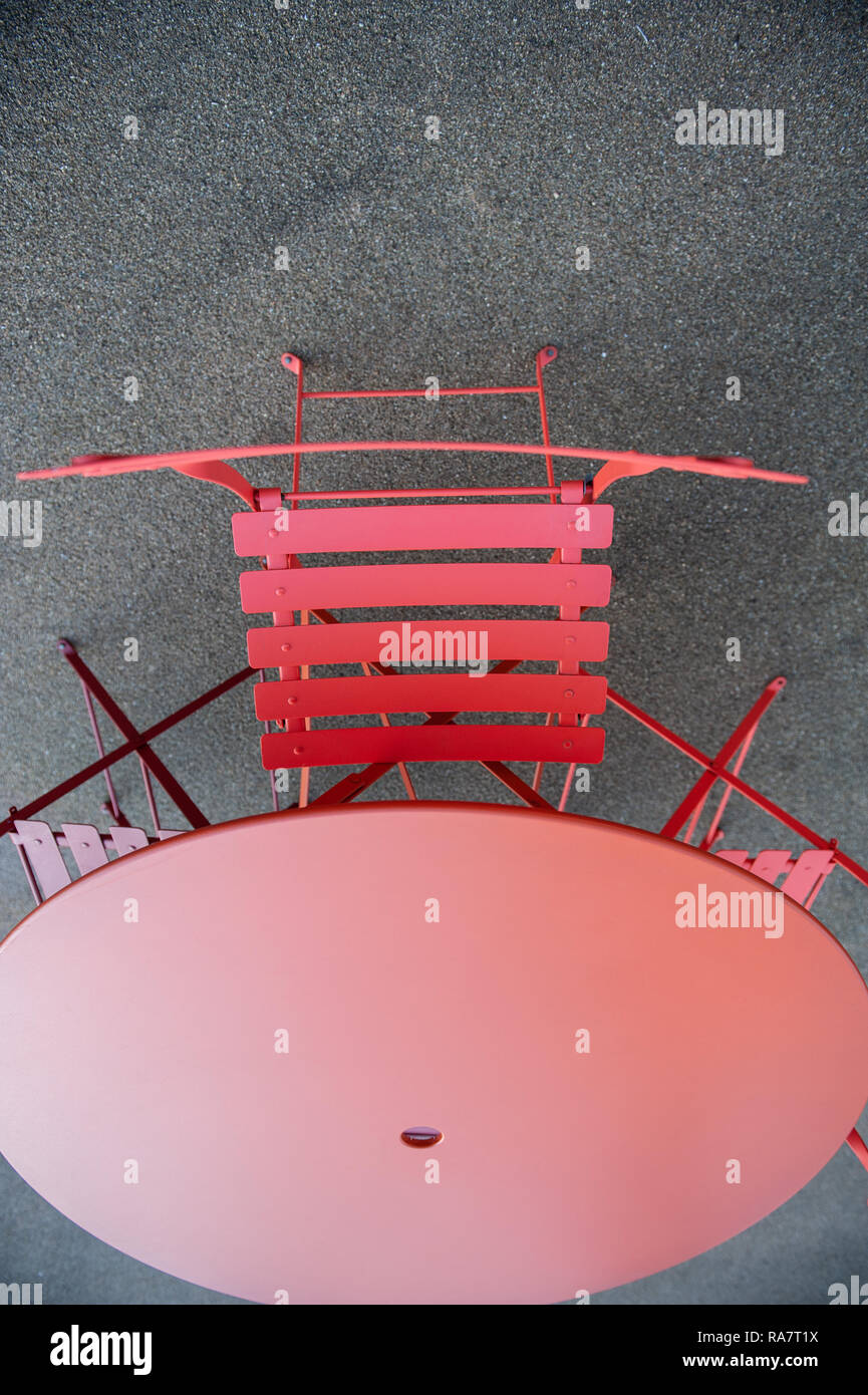 Red cafe table and chairs out of doors on tarmac floor. - Stock Image
