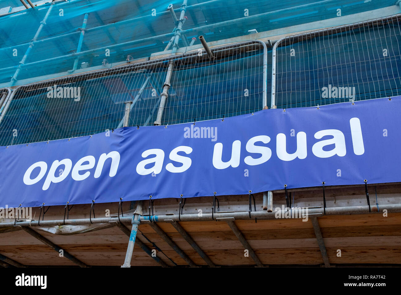 Shop in scaffolding with open as usual sign - Stock Image