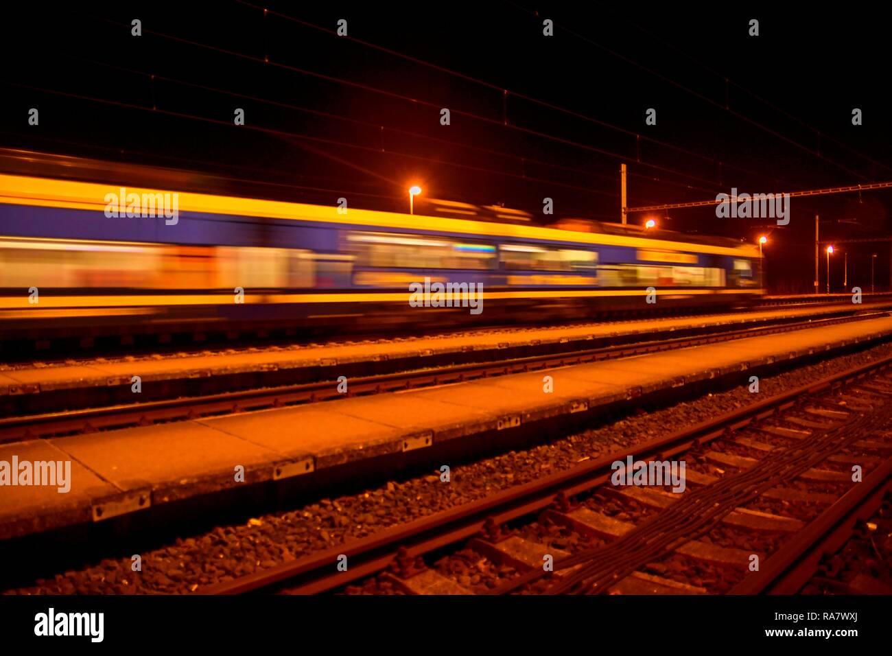Passenger train on railroad tracks at night  Blurred motion - Stock Image