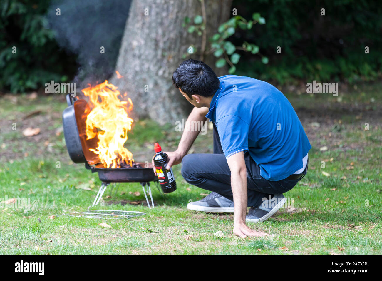 Man ignites a charcoal grill with liquid grill lighter and recoils from the flame, - Stock Image