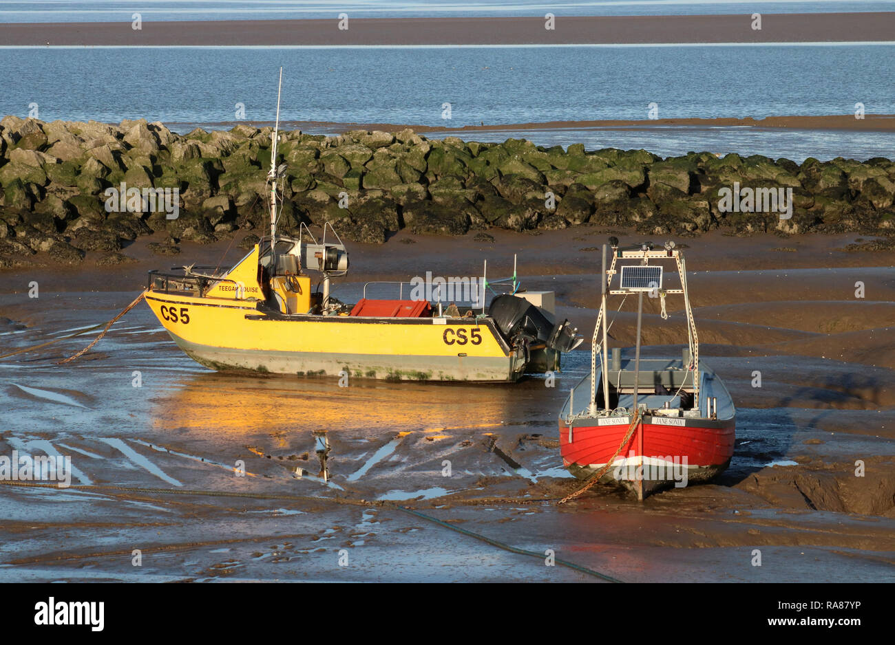 Two small fishing boats, one yellow and one red, on mud at low tide on New Year's Day by the Stone Jetty at Morecambe, Lancashire, United Kingdom. Stock Photo