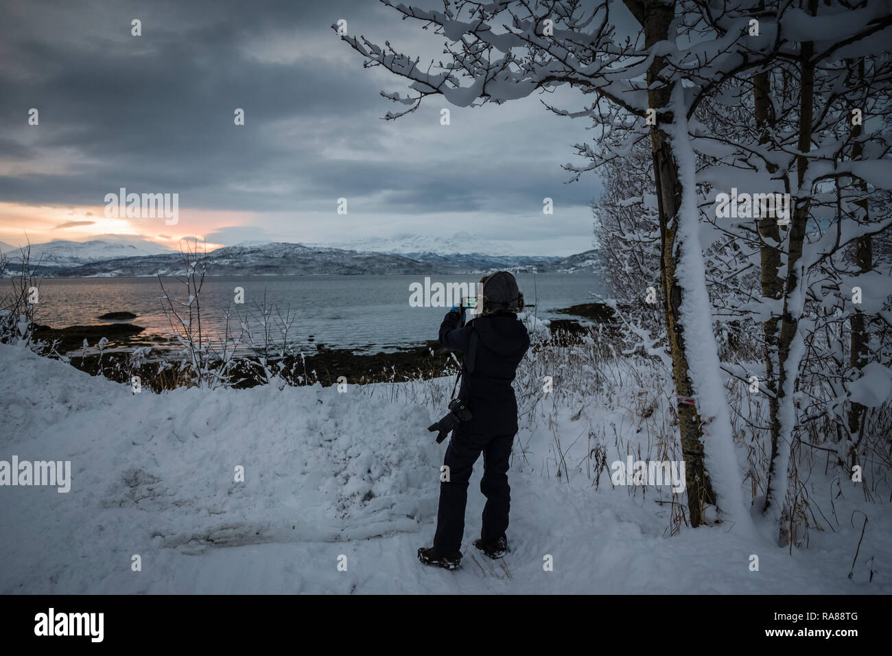 Female photographer capturing winter snows at Finnsnes, Norway. Stock Photo