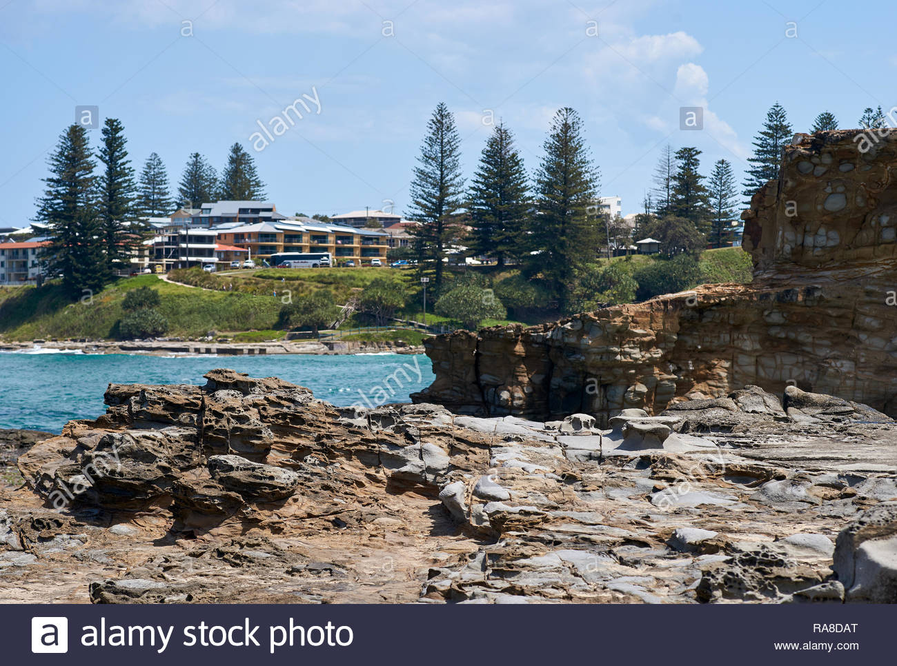 The wave-washed rocks of the coastal headland between Turners and Main beach; Yamba, NSW, Australia. Pacific Ocean eroding sandstone rock formation. - Stock Image