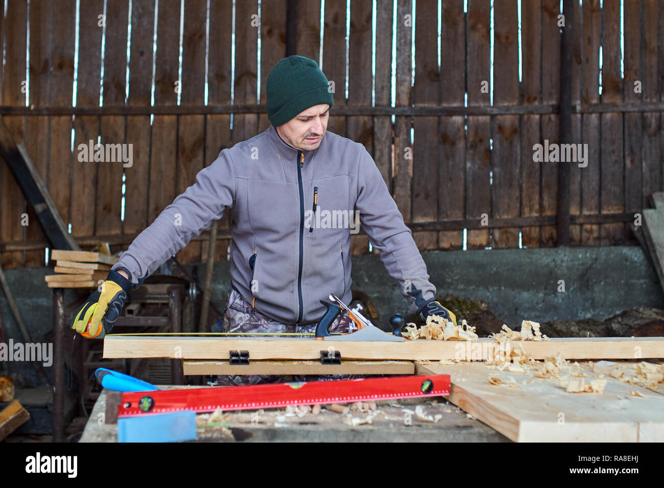 Woodworker measuing and planing his project in the workshop - Stock Image