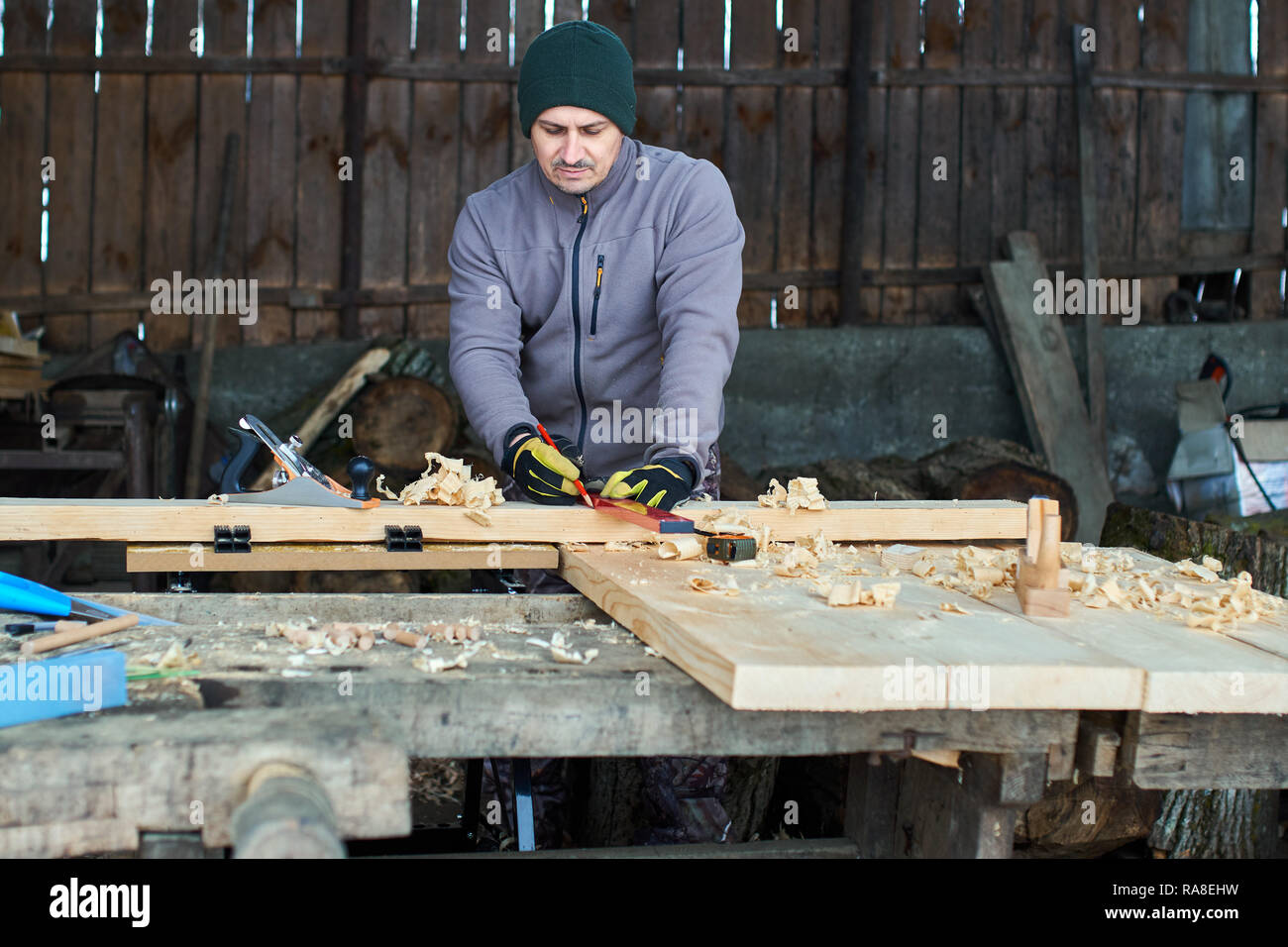 Woodworker measuring and drawing lines on his cabinet project - Stock Image