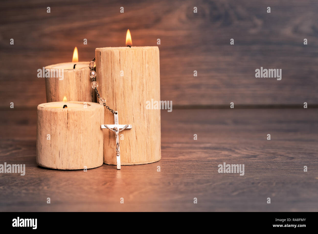 Silver rosary with Jesus on the Candle at wooden table,religion concept,vintage style with split toning. Stock Photo
