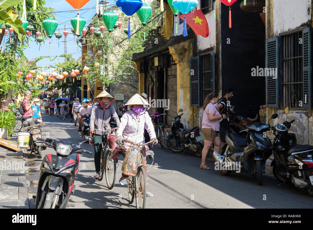 Typical street scene with local women riding bicycles in narrow street in old quarter of historic town. Hoi An, Quang Nam Province, Vietnam, Asia - Stock Image