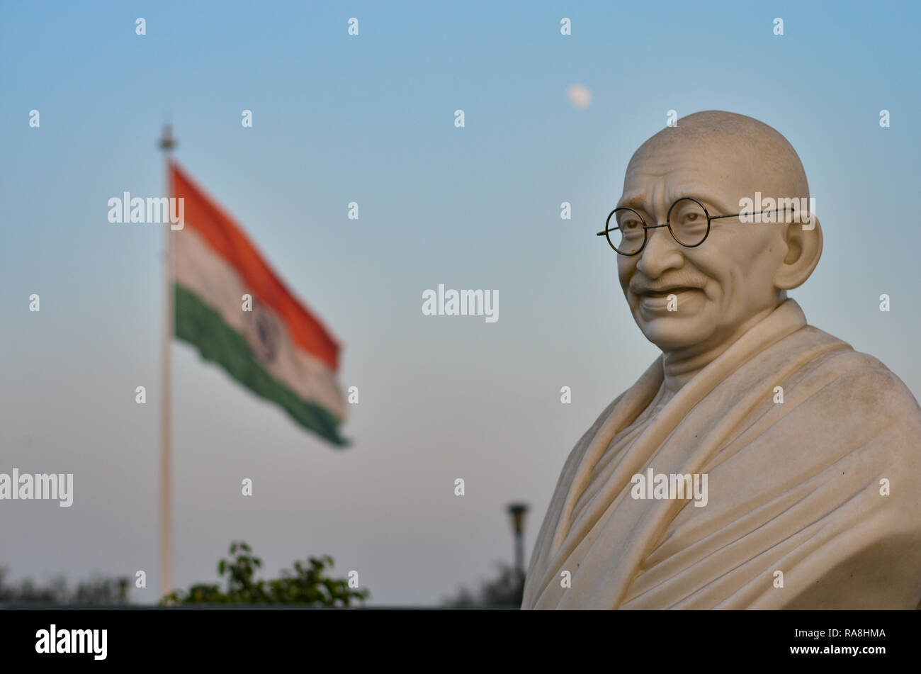 Bust of Gandhi statue with Indian tricolor in the background in Connaught Place, Delhi, India. Mahatma Gandhi is the Father of nation. - Stock Image