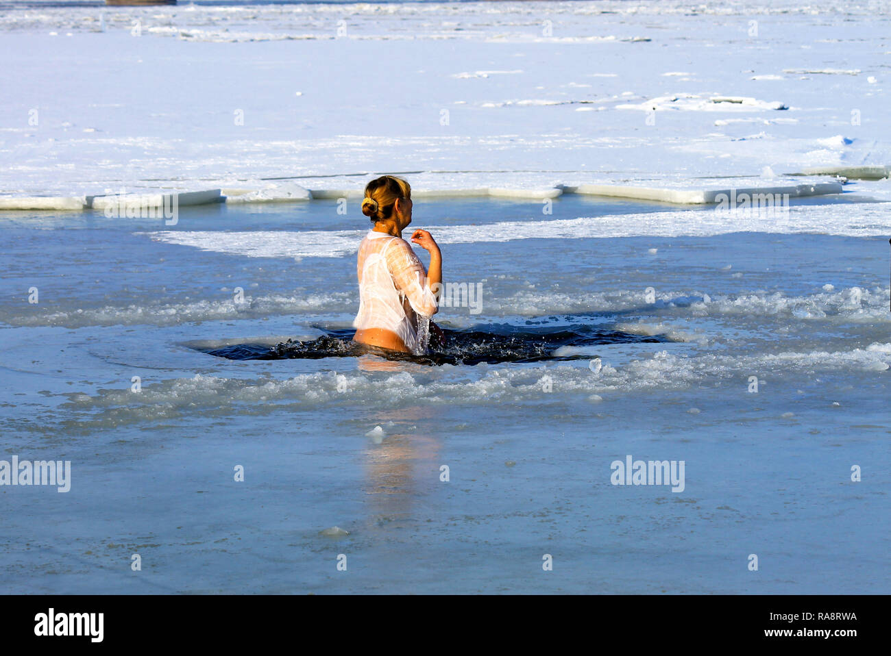 Winter sport. A woman swims in the winter river covered with ice during the holiday of Epiphany. Hardening - Stock Image