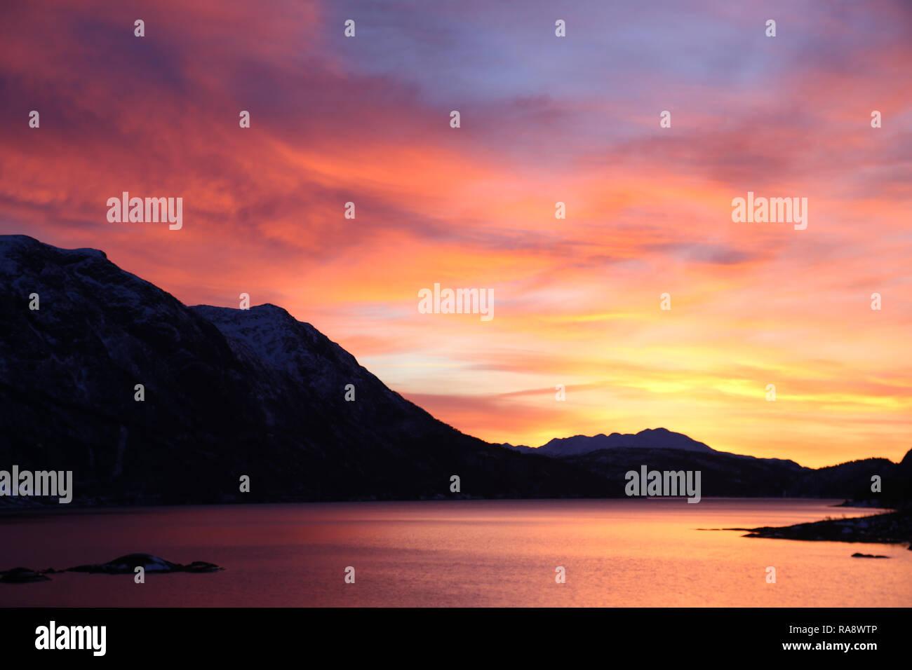 Stunning sunrise over lake and mountains - Stock Image
