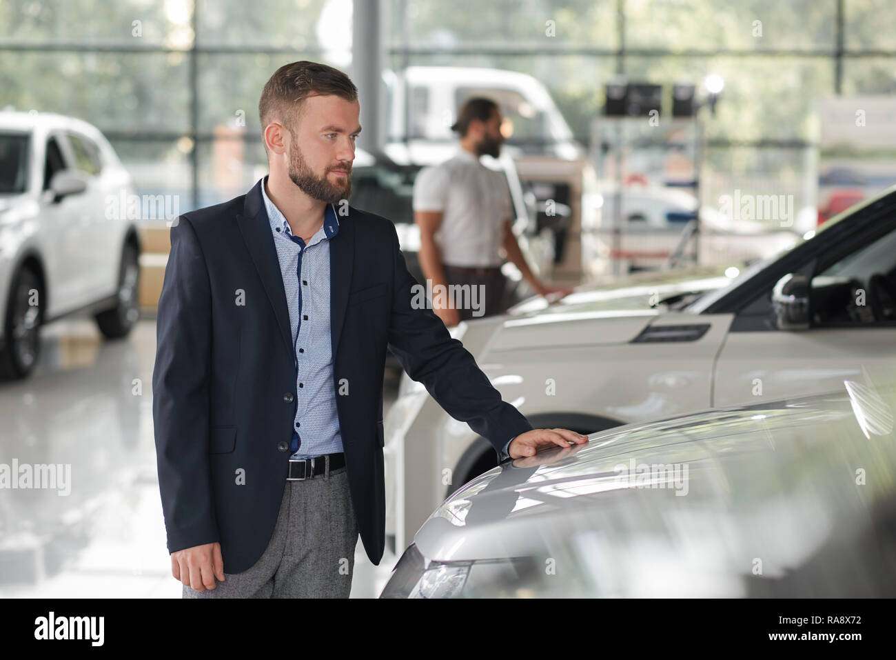 Men looking for vehicles in car showroom. Bearded man wearing in dark blue jacket looking at car and holding hand on car hood. People observing automobiles for purchase. - Stock Image