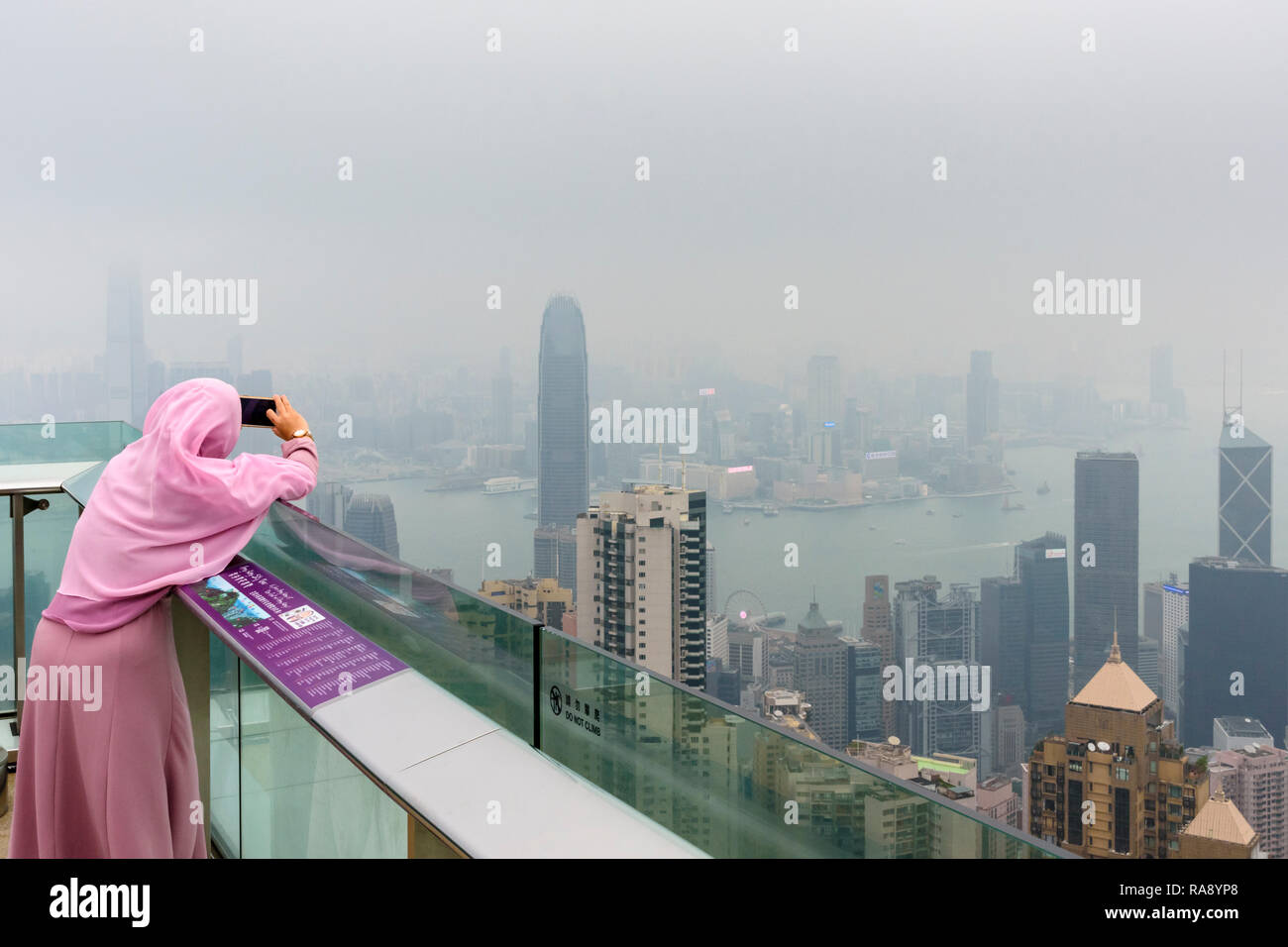 Woman takes a mobile phone photo on the deck of The Peak Tower viewing platform restricted by the haze from air pollution, Hong Kong - Stock Image