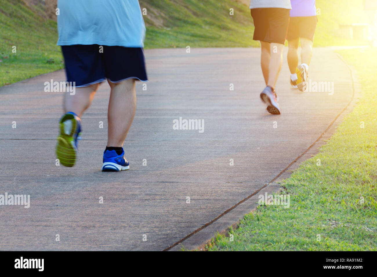 Fat man jogging, catching up with thin men. Low angle view of runners running in park. Blurred feet motion group of runners, Fitness and healthy - Stock Image
