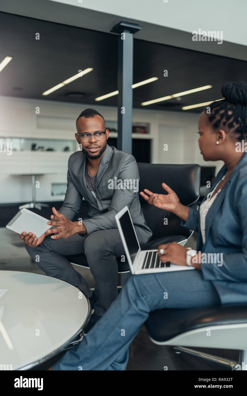Two african business people talking seriously with hand gestures during a meeting using their laptop and tablet Stock Photo