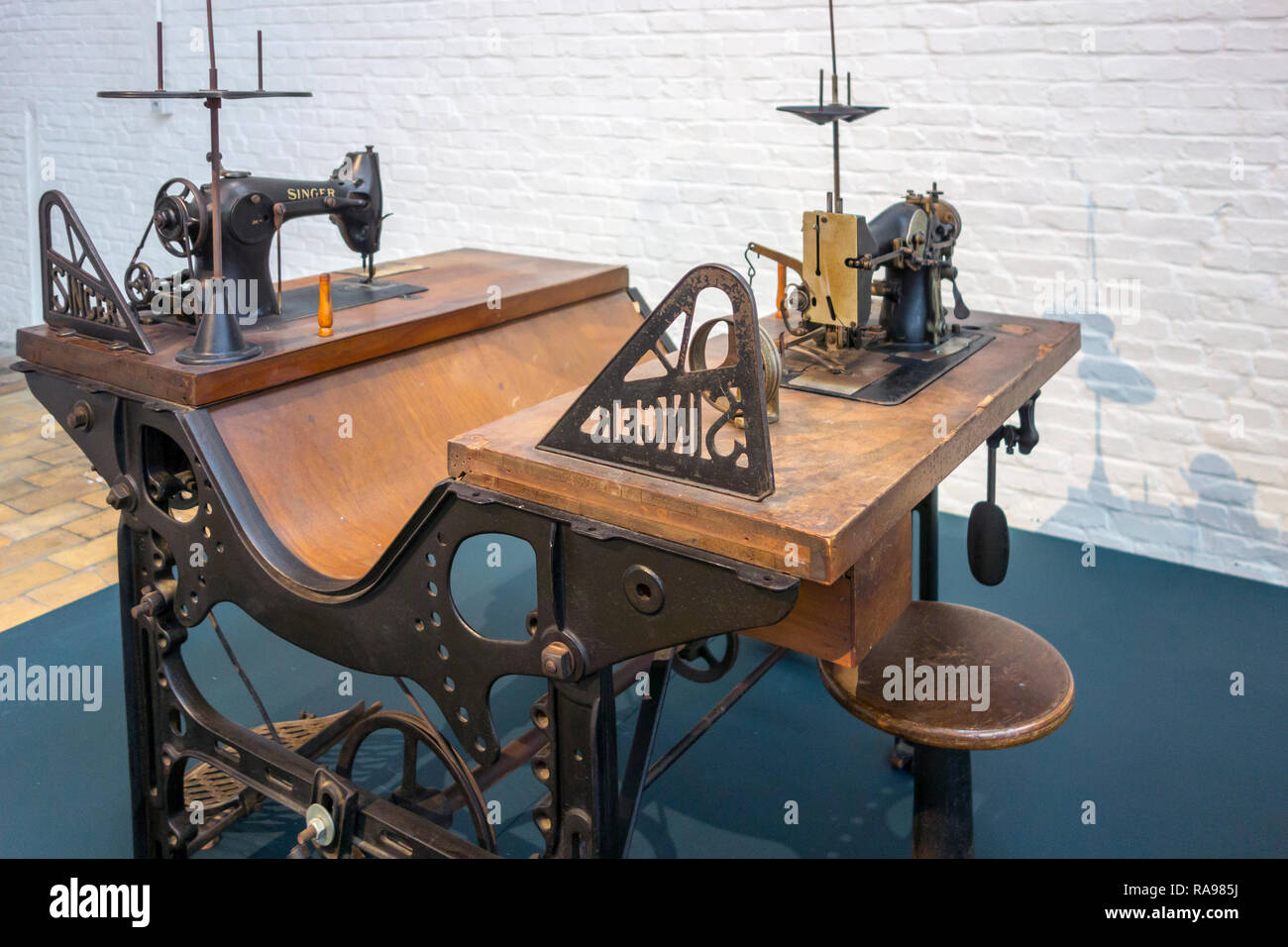 20th century industrial needlework table with two Singer sewing machines in textile factory at MIAT / Industriemuseum, Ghent, Belgium - Stock Image