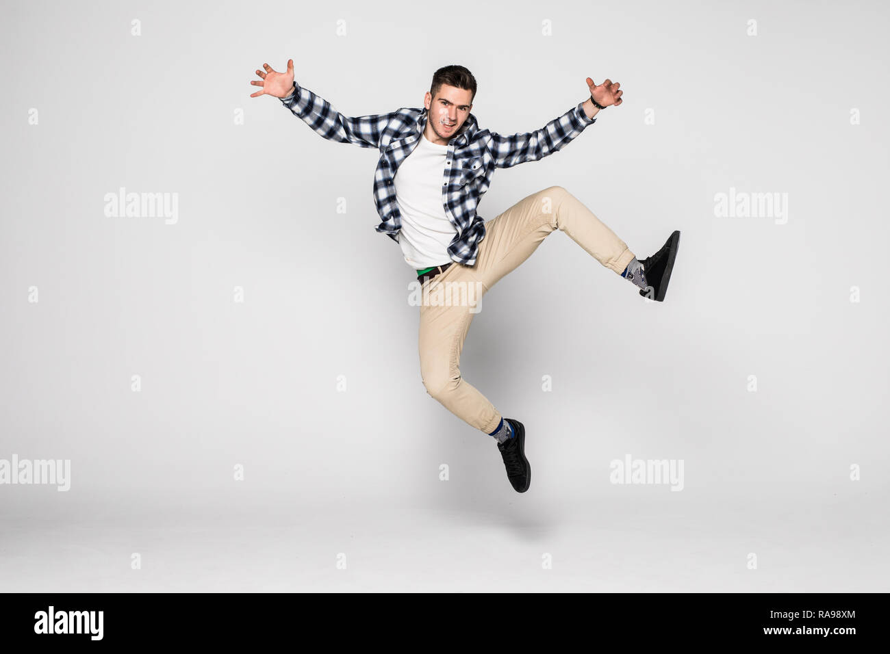 Dynamic, image. Full length, legs, body, size profile side view portrait of handsome attractive man jupm isolated on white background - Stock Image