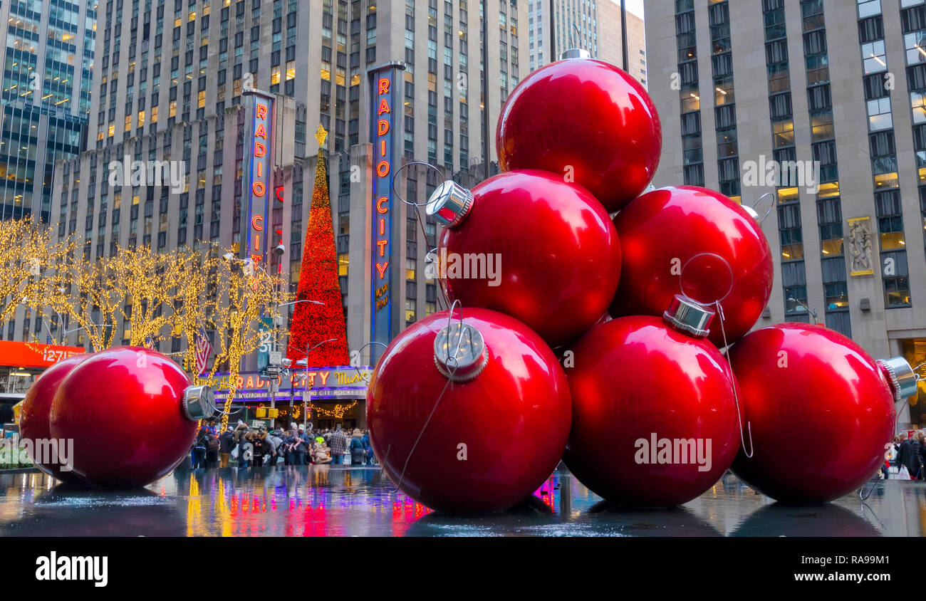 Giant Red Christmas Ornaments near Radio City Music Hall on 6th Avenue, New York City. - Stock Image