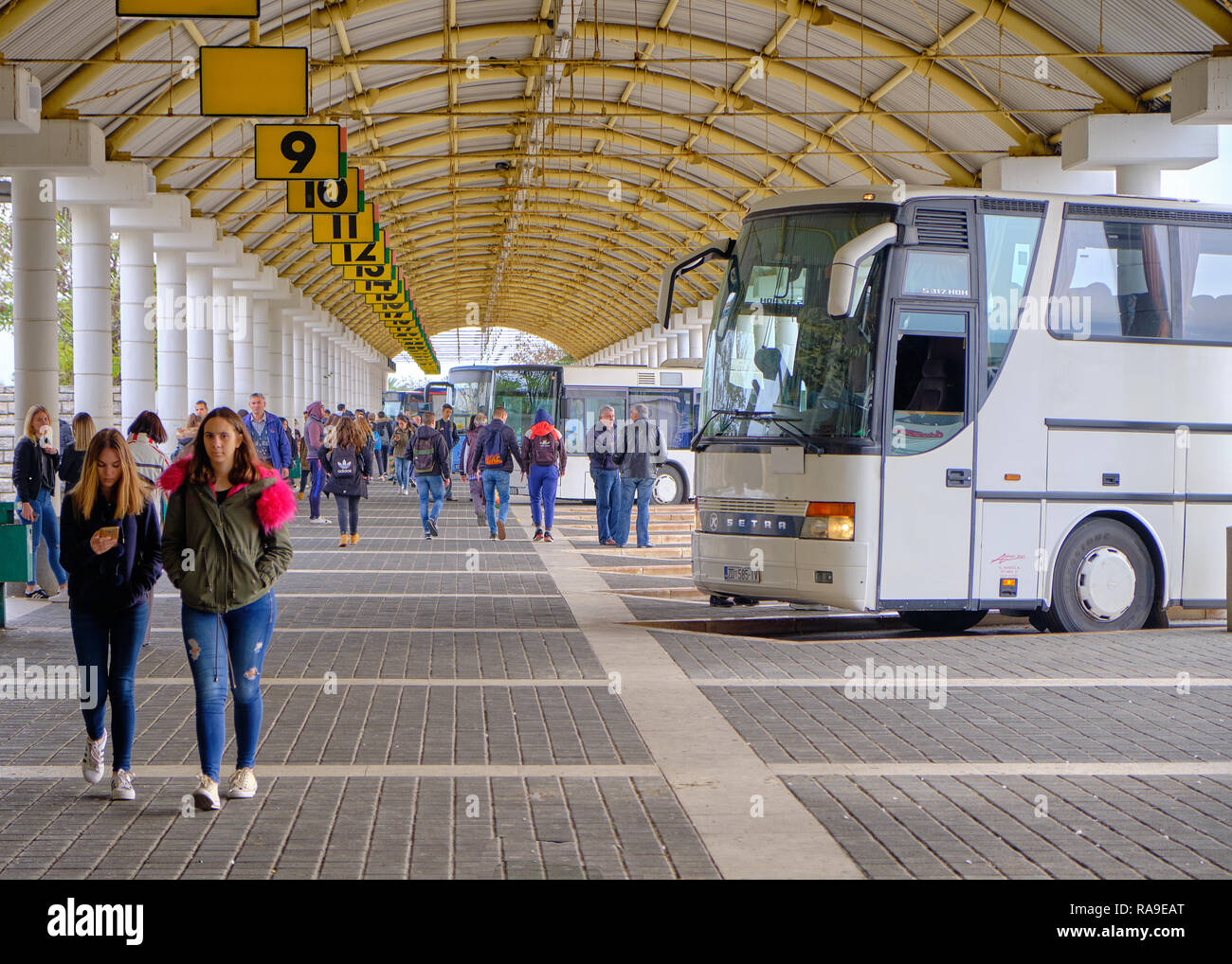 The long distance bus terminal platform 9 and up, with bus waiting, and passengers arriving, Leading line of the numbers and arched dome architecture - Stock Image