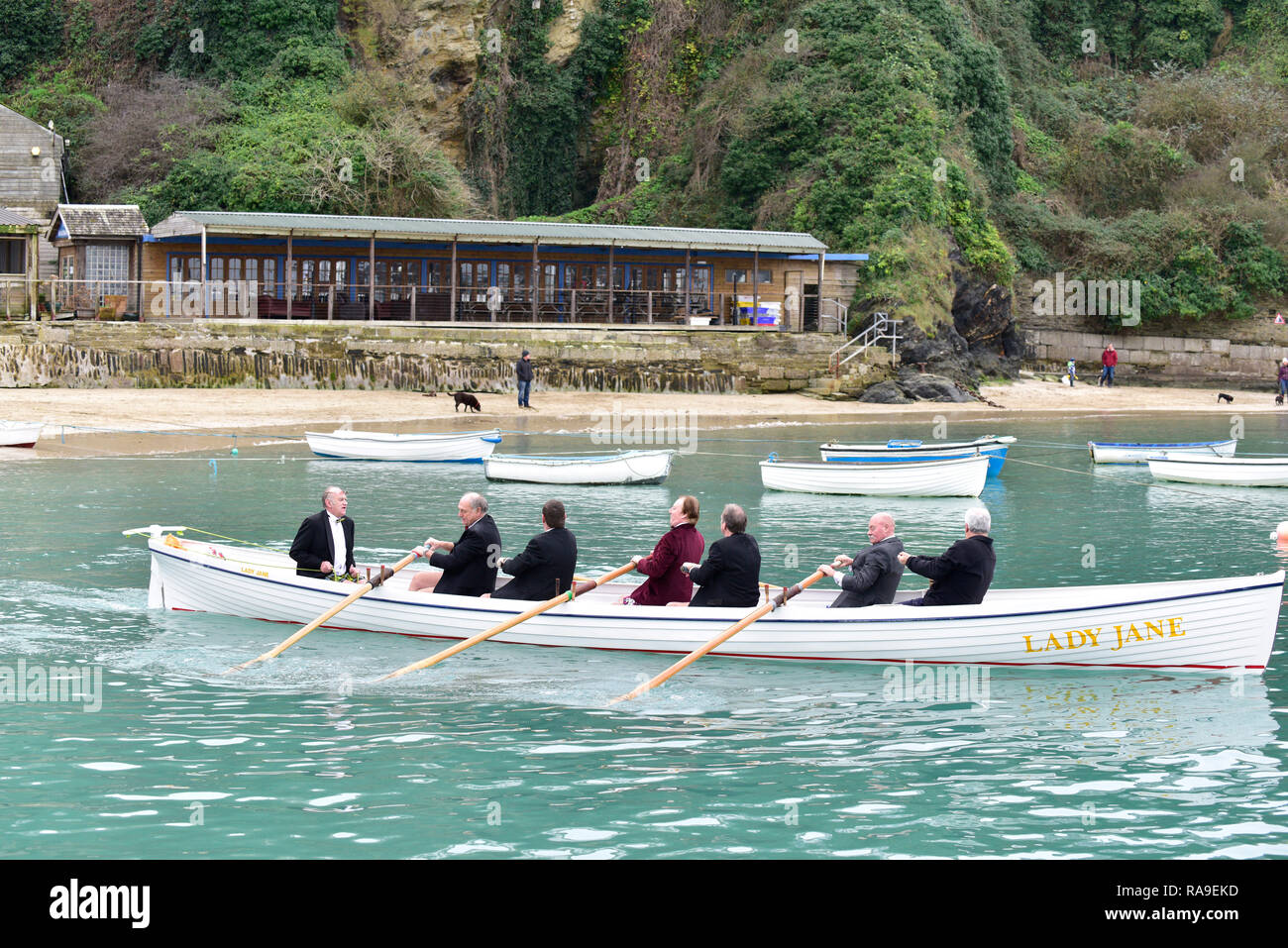 Senior members of Newquay Rowing Club wearing tuxedos setting off from Newquay Harbour on their annual 'Port Run' in a traditional Cornish Pilot gig. - Stock Image