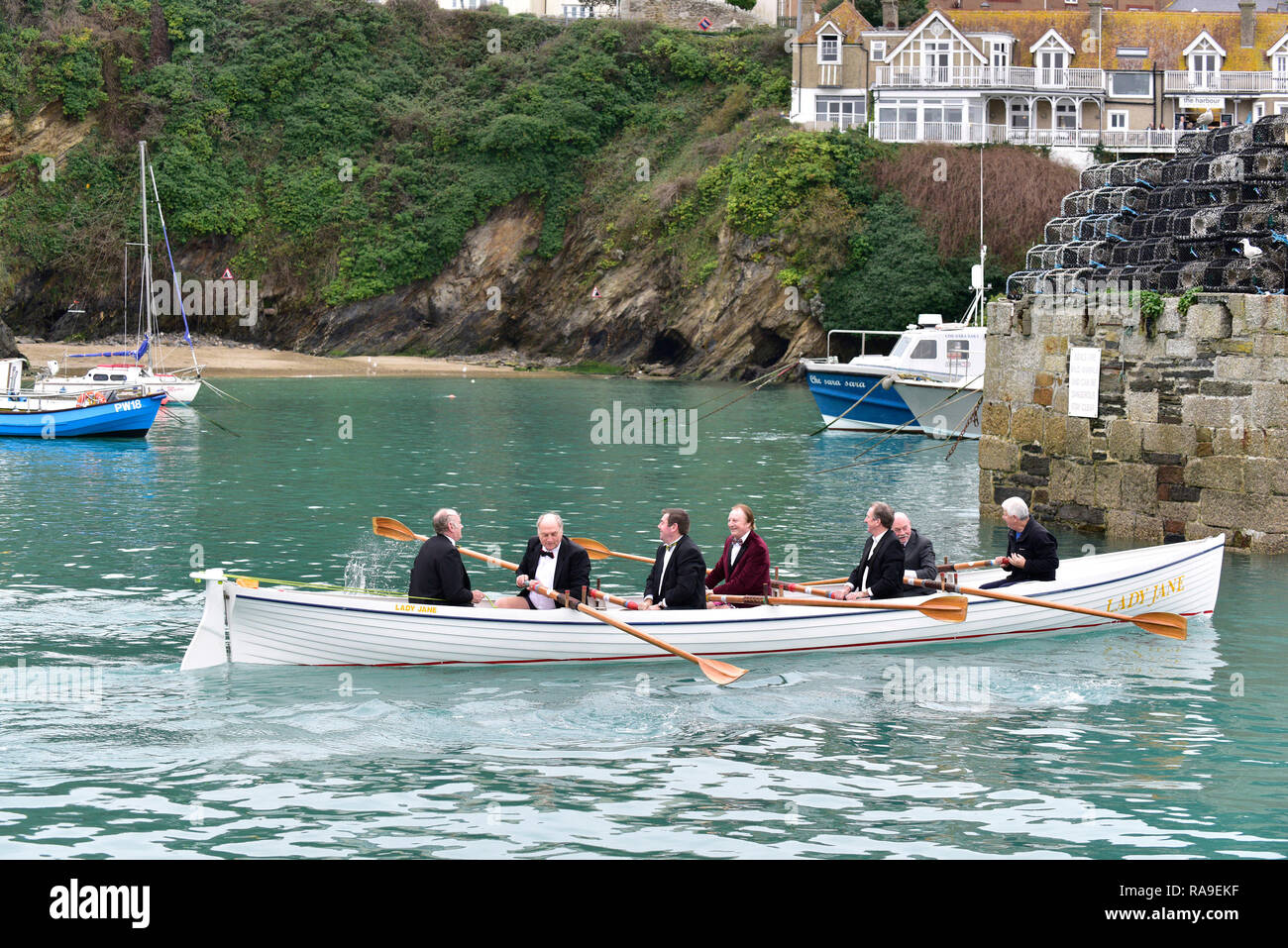 Senior members of Newquay Rowing Club wearing tuxedos setting off from Newquay Harbour on their annual 'Port Run' in a traditional Cornish Pilot g - Stock Image