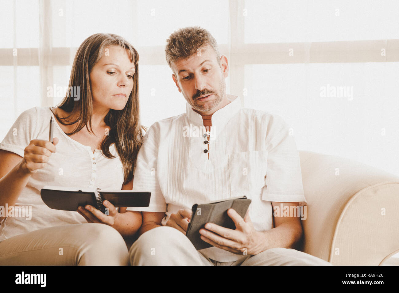 Husband and wife on a couch in their apartment with a tablet and a notepad - Stock Image