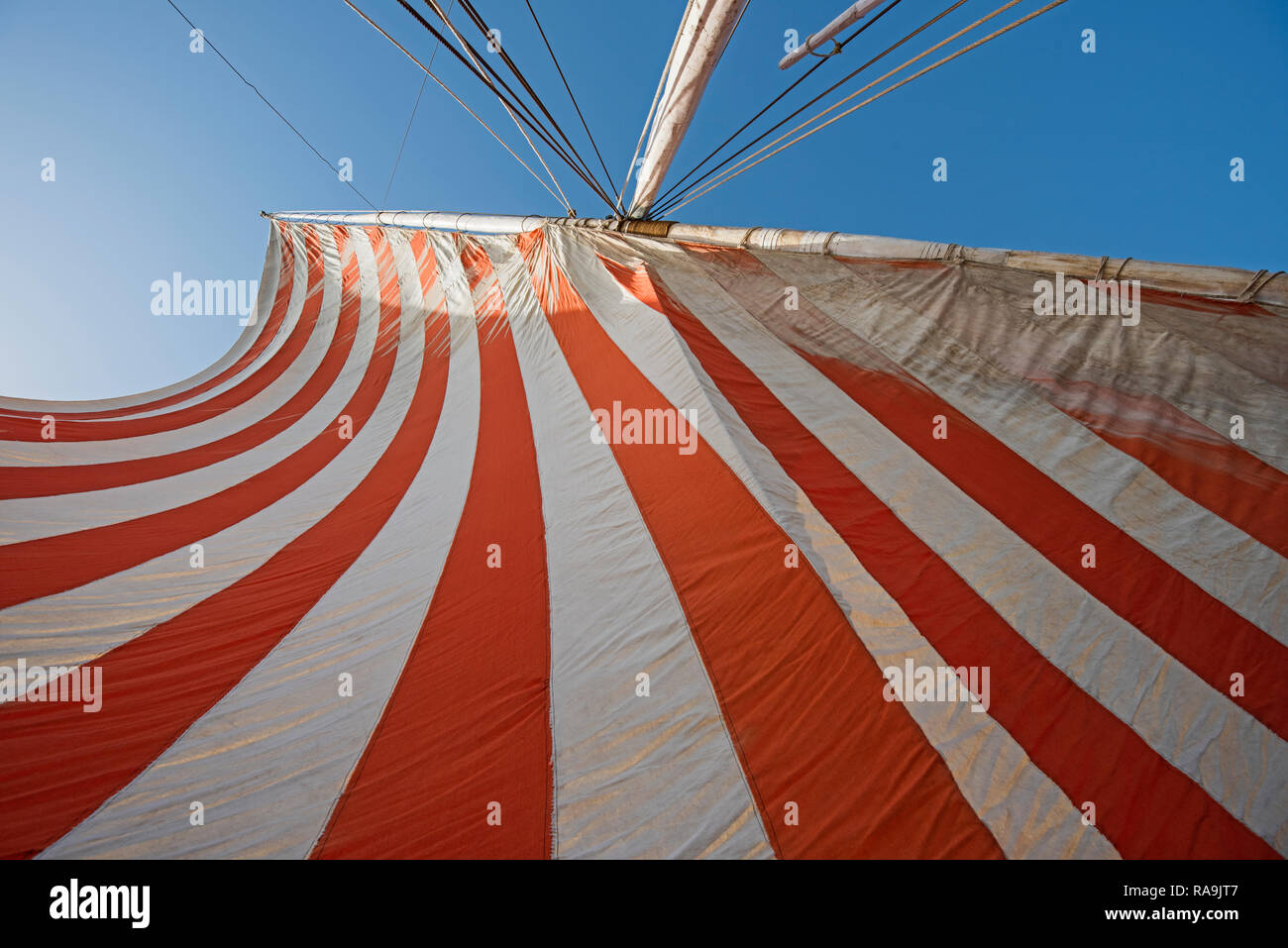 Abstract view of traditional striped cloth sail on egyptian wooden boat with mast and blue sky background - Stock Image