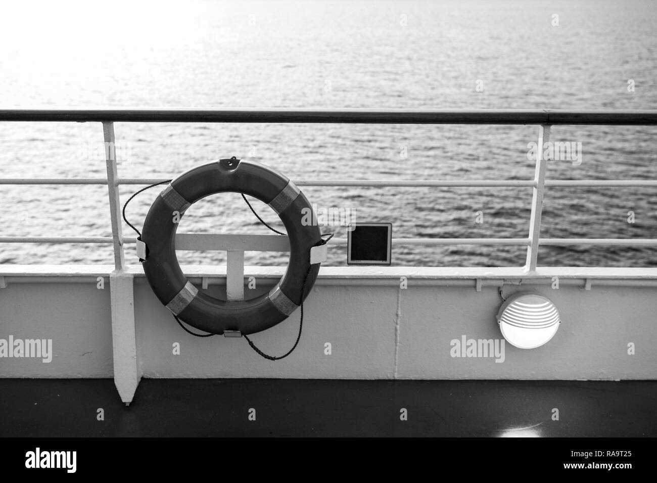 Buoy or lifebuoy ring on shipboard in evening sea in miami, usa. Flotation device on ship side on seascape. Safety, rescue, life preserver. Water travel, voyage, journey. Wanderlust, vacation, trip. - Stock Image