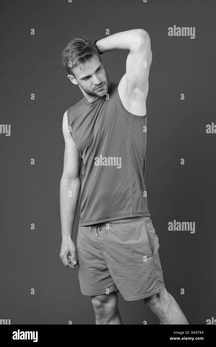 Man confident in his antiperspirant. Guy checks dry armpit satisfied with healthy skin. Prevent, reduce perspiration. No sweat - deodorant works. Sportsman after training pleased with antiperspirant. - Stock Image