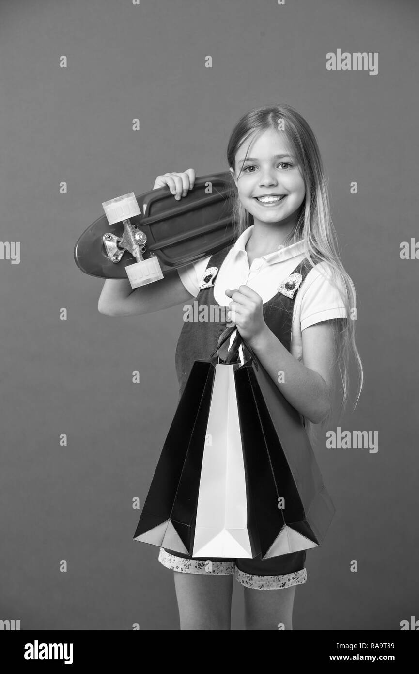 Little child smile with paper bags and skateboard on violet background. Happy girl with skate board and shopping bags. Shopping and black friday. Sport and active games. Happy shopaholic girl - Stock Image