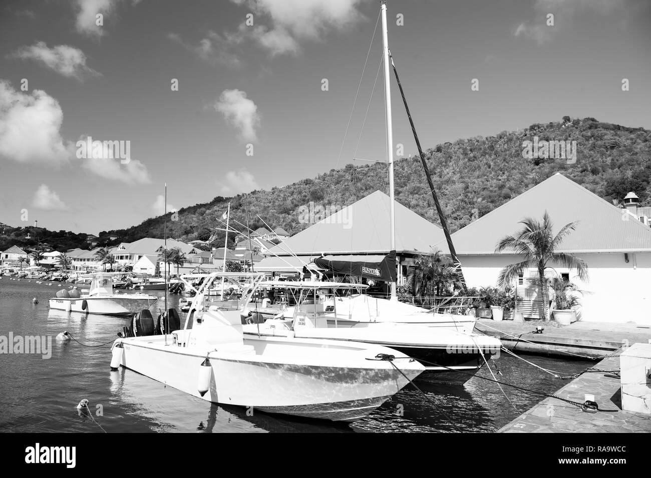 Gustavia, st.barts - January 25, 2016: sailboats and yachts anchored at sea pier on tropical beach. Yachting and sailing. Luxury travel on yacht. Summer vacation on island. Water transport and vessel. - Stock Image