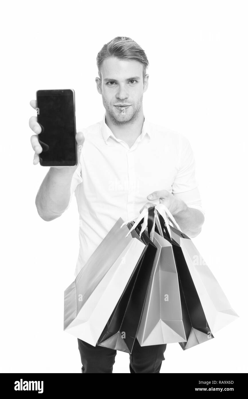 Guy buy fashionable clothes online with smartphone. Man happy client received packages purchases. Online shopping concept. Man takes advantages online shopping. Guy carries bunch colorful bags. - Stock Image