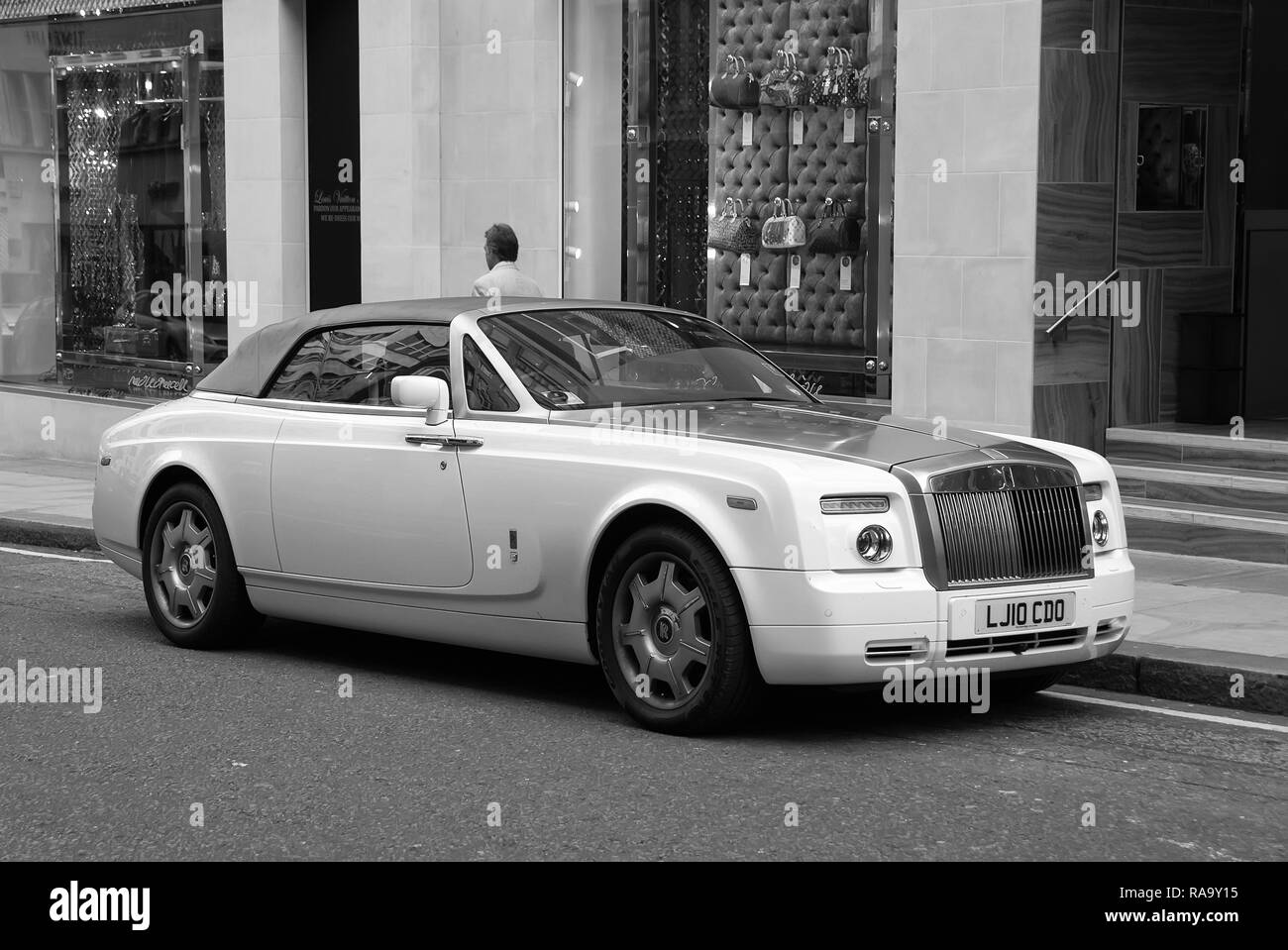 London, United Kingdom - February 25, 2010: car parked at shop window. Luxury automobile on city street. Motor transport and transportation. Travelling or trip and wanderlust. Stock Photo
