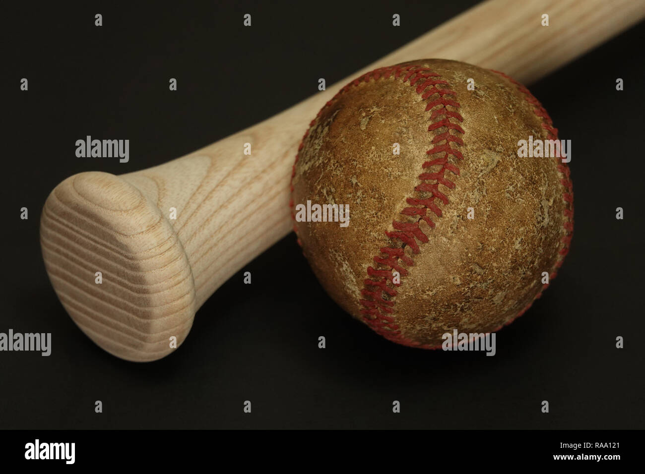 An old and well used baseball is shown next to a new, wood baseball bat, set against a black background. - Stock Image