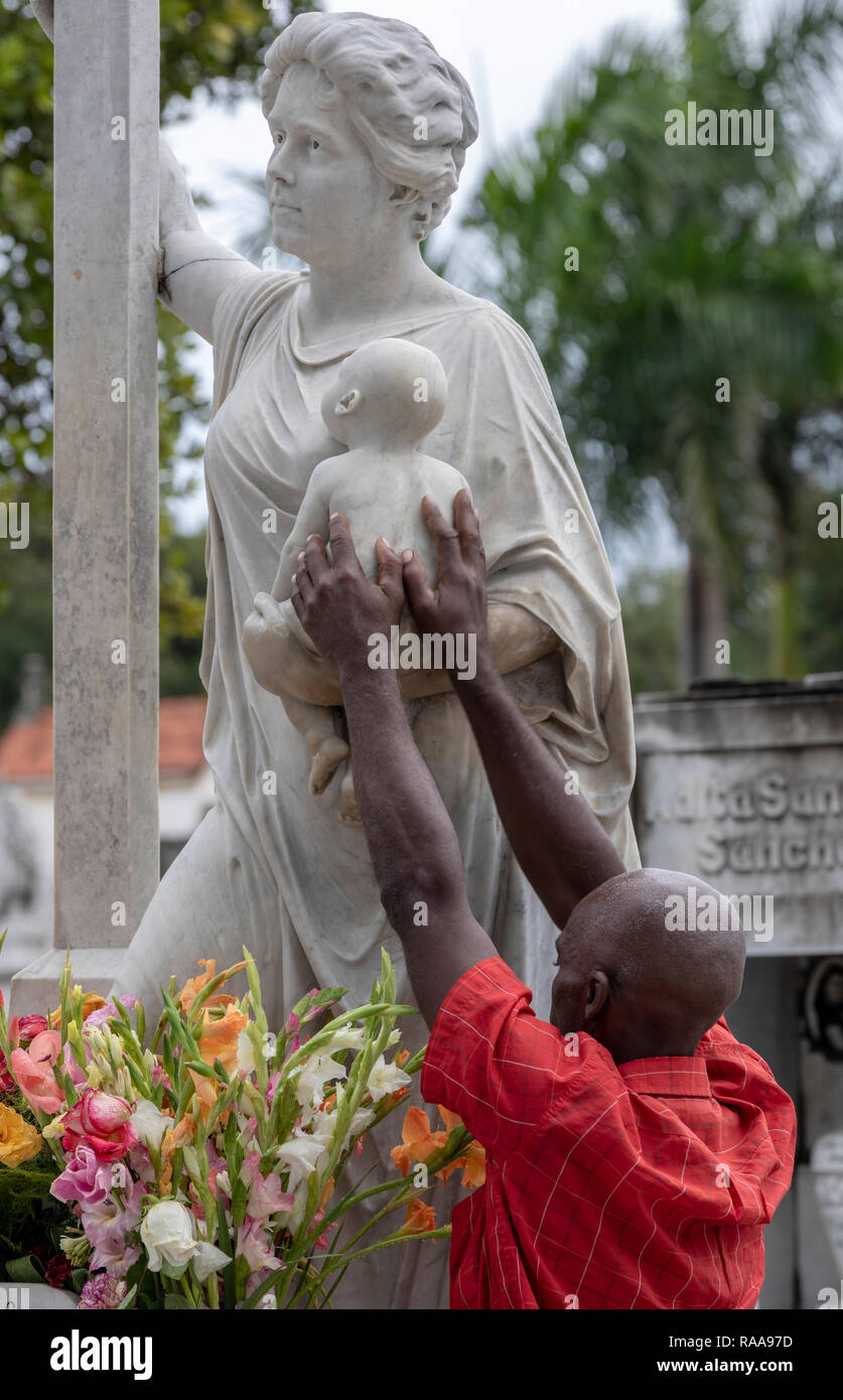 Pilgrim at tomb of La Milagrosa, Colon Cemetery, Havana, Cuba - Stock Image