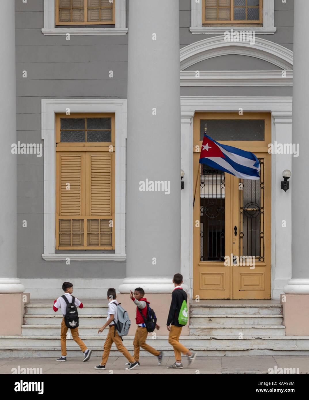 Schoolboys walking in front of Collegio San Lorenzo, Plaza Jose Marti, Cienfuegos, Cuba - Stock Image