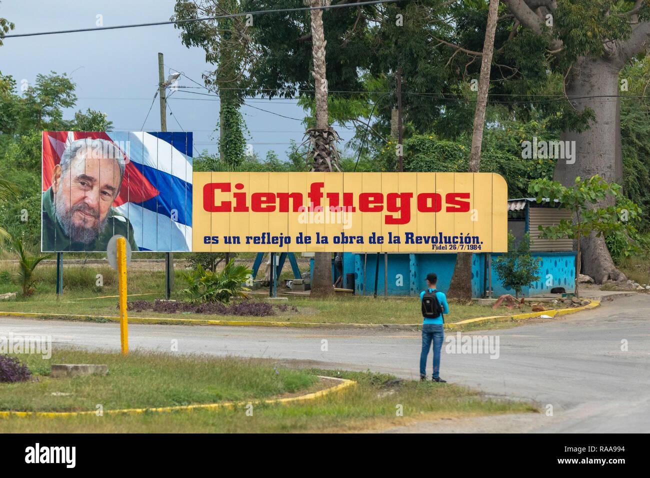 man waits for bus under Fidel Castro propaganda billboard - Stock Image